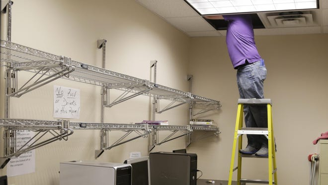 A worker from Main Street Management moves wiring so Lafayette Transitional Housing Center can relocate computers that the clients use.
