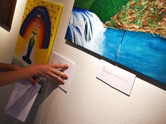 Joan Swenson, with Tallgrass Recovery, puts up artist