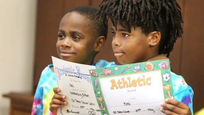 On the last day of Saint Peter Claver Latin School for Boys in Over-the-Rhine, students in the K-8th grade were given their awards, ranging from art to athleticism to academic effort. First graders Rallin Smith (left) and Kosi Watts pose for a photo during the final celebration.