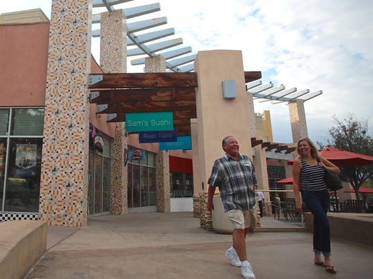 Customers stroll through the outdoor walkway of The River shopping mall in Rancho Mirage on Tuesday afternoon. The shopping center on Highway 111, between Las Palmas and Bob Hope drives, is considered Rancho Mirage's downtown. It has struggled in recent years, especially with the departure of Borders bookstore in 2011. The center's new owner, CheerLand Investment Group, is working to revive the center — a task taking longer than they had expected.