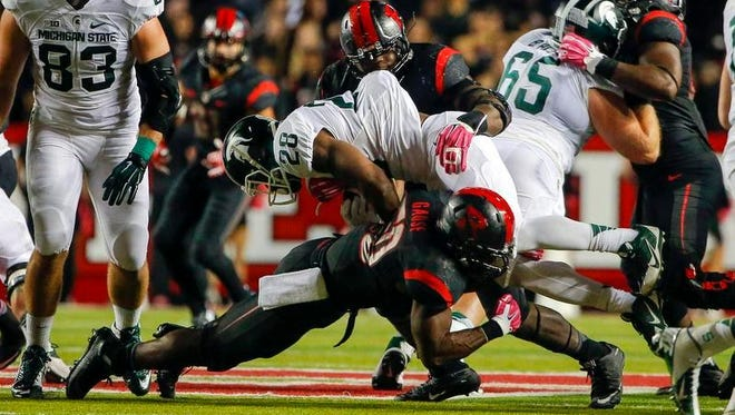 Oct 10, 2015; Piscataway, NJ, USA; Rutgers Scarlet Knights linebacker Quentin Gause (50) stops Michigan State Spartans running back Madre London (28) for a loss at High Points Solutions Stadium.