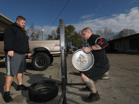 Kyle Rojas works on keg lifting as a part of training with the Barbaric Barbell Strongman Team as workout partner Jesse Taber watches at Tallahassee Strength Club at Boot Camp Fitness and Training on Feb. 2, 2018.