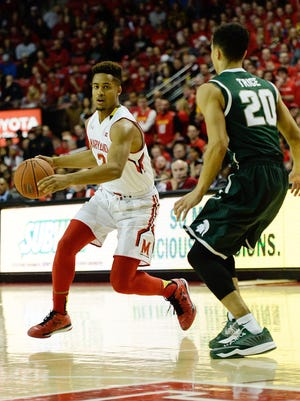 Maryland guard Melo Trimble dribbles as Michigan State guard Travis Trice defends during the first half.