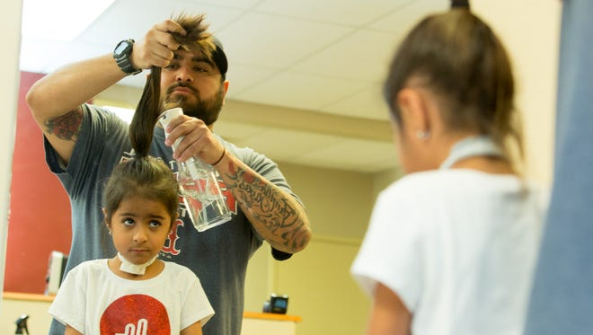 Xavi Olivas, of El Paso, does the hair of his twin daughters Emma, 6, and Kaitlin, (not pictured), on Saturday, February 10, 2018, during a Daddy-Daughter Braiding workshop at Computer Career Center.