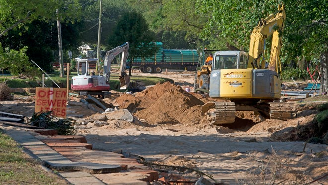 Utility crews work in the Cordova Park area to restore the infrastructure on Piedmont Road. The heavy rains and floodwaters scoured out much of the roadway and severely damaged the underground utilities in the area.