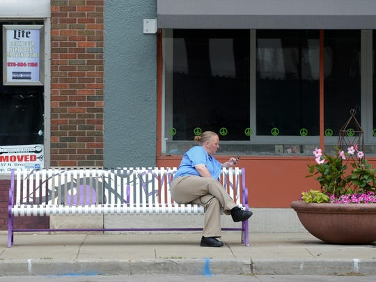 Kerri Priem uses her phone while waiting on one of the newly painted benches on North Broadway in Green Bay.