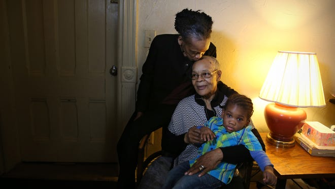 Ruthie Osborne, 76, gets a kiss from daughter Donnie Loyd, as she sits with her and Christopher, a 19-month-old she is raising, in their Rochester home Wednesday, Feb. 22, 2017.  Osborne is raising the boy for a woman who is in jail.