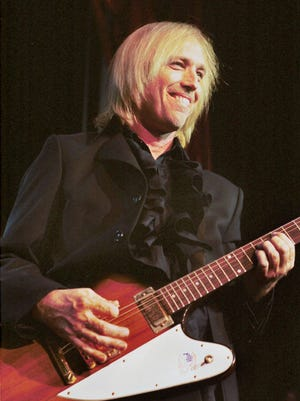 Tom Petty puts The Heartbreakers through their paces during a June 18, 1999, concert at Pine Knob Music Theater in Clarkston, Michigan.