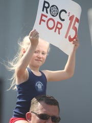 Labor Day marchers Juliana Shattuck, 6, and Chris McCamic show support for the Fight for $15 movement in Rochester last year.