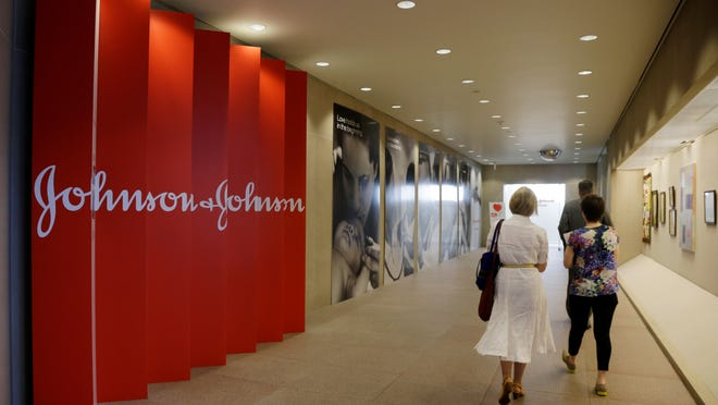 People walk along a corridor at the headquarters of Johnson & Johnson in New Brunswick, N.J. Johnson & Johnson on Tuesday, Jan. 20, 2015 said its fourth-quarter profit dropped 28 percent as lower sales overseas, mainly because of unfavorable currency exchange rates, dragged down revenue for its consumer and medical device businesses.
