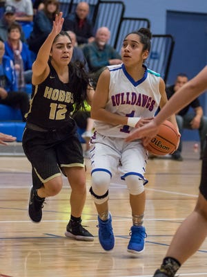 Las Cruces High's Brooke Salmon breaks to the basket as Hobbs' Desiree Martinez chases her down Friday night at Las Cruces High School.