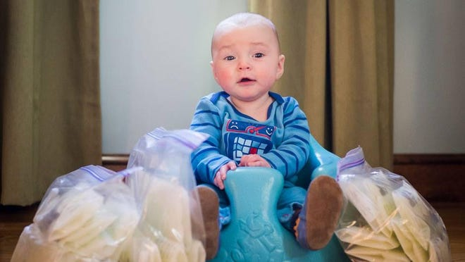 A happy baby sits surrounded by bags of frozen mother's milk.