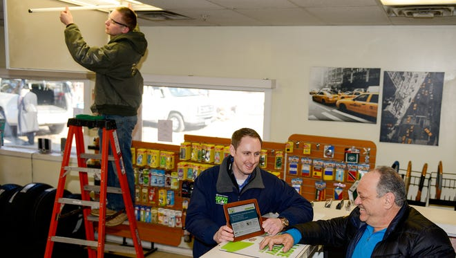 Adam Smith, Orange and Rockland employee, speaks with Sam Naemit, the owner of Sam's Towing and  Automotive in Spring Valley.