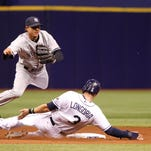 New York Yankees second baseman Brian Roberts (14) forces out Tampa Bay Rays third baseman Evan Longoria (3) and throws the ball to first base for a double play during the fourth inning at Tropicana Field.