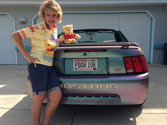 Deb Hoffmann of Vernon stands next to her lifelong friend, Winnie the Pooh, sitting atop her Ford Mustang that bears personalized plates referring her extensive collection. Hoffmann is considered by the Guinness Book of World Records to have the most Pooh collectibles.