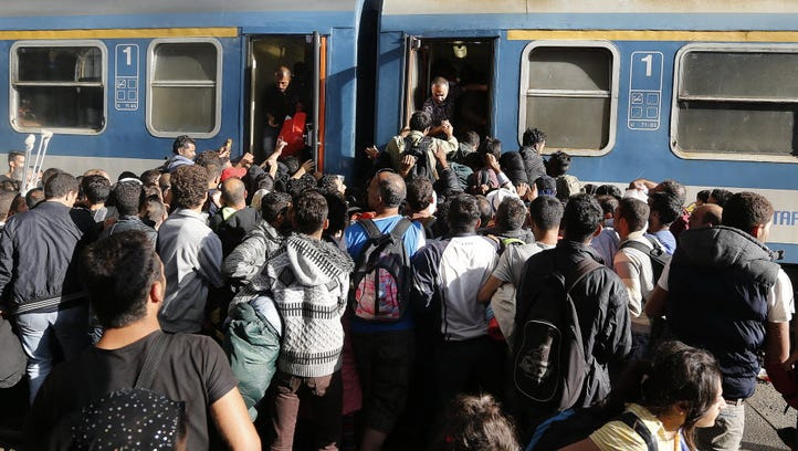 Migrants try to board a train at the railway station
