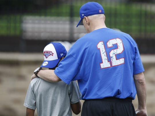 Jim Kelly puts his arm around Jeremy Copeland, 10, during his Jim Kelly Football Camp on July 15, 2014 at St. John Fisher College in Pittsford.