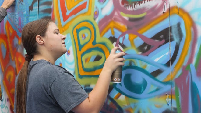 WNMU student Chelsea Boone paints an eye at the the spray painting workshop held by Rose B. Simpson at the university on Friday.