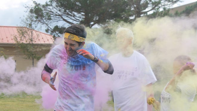 Nathan Jackson runs through the cloud of purple and yellow chalk dye during Friday's color run Homecoming event at WNMU.