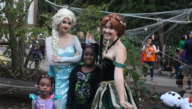 Disney princesses Elsa and Anna, from Neverland & Company, pose with Morgan Franklin, 6, right, and her sister Avery, 2, left, at Zoo Knoxville's BOO! at the Zoo on Saturday, Oct. 16, 2016. Morgan was dressed as a cat and Avery was dressed as Disney princess Ariel.