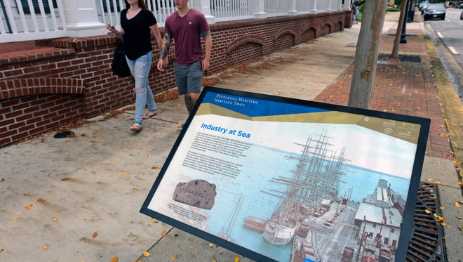 Rachel Daily and Wathew Jackson walk up Palafox Place to the Pensacola Maritime Heritage Trail marker. The heritage trail will feature 10 panels full of historical information that will be erected along Main Street/Bayfront Parkway.