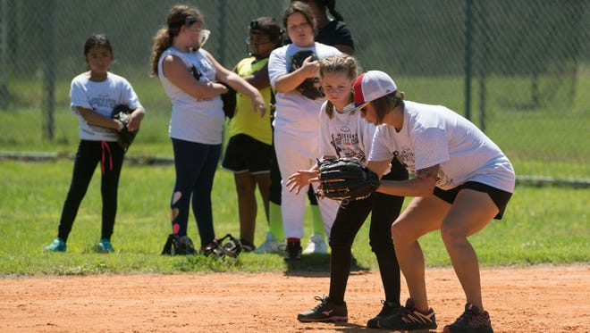 Marine Master Sgt. Melisa Schwinden of the All Marine Women's Softball Team gives tips to Emma Vignolo,10, Sunday, August 5, 2018 during their softball clinic at Myrtle Grove Ballpark.