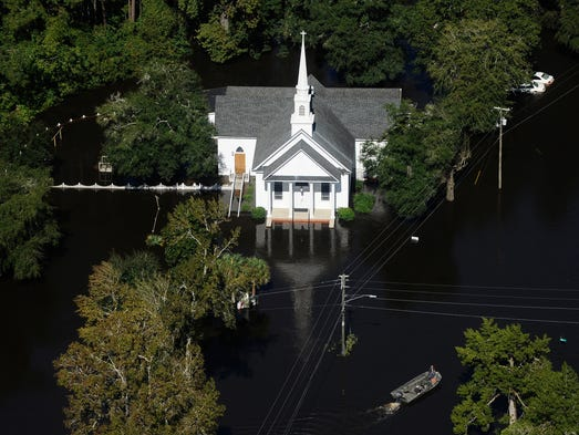 A boat passes a church in Nichols, S.C., Monday, Oct.