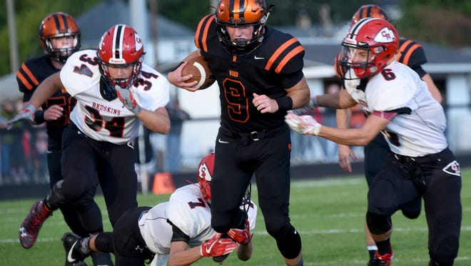 Ridgewood's Kaden Smith tries to dodge Coshocton's Ethan Murray, Gaven Williams, and Andrew Kittell during Friday night's game in West Lafayette. The Generals won 34-19