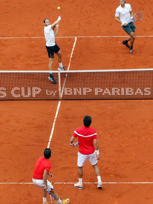 Germans Jan-Lennard Struff, and Tim Puetz, top, during their match against Spain's Marc Lopez and Feliciano during a World Group Quarter final Davis Cup tennis match at the bullring in Valencia, Spain, Saturday, April 7, 2018. (AP Photo/Alberto Saiz)