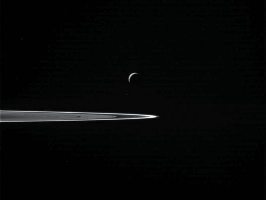 This Wednesday, Oct. 28, 2015 image provided by NASA shows Saturn's moon Enceladus, center, as the Cassini spacecraft prepared to make a close flyby of the icy moon. A portion of the planet's ring is at right. (NASA/JPL-Caltech/Space Science Institute via AP)