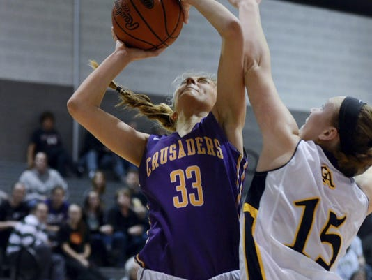 Lancaster Catholic's Caroline Scarff, left, draws contact en route to the bucket against Katie Gelsinger, of Greencastle-Antrim, on Sunday during the District 3 Class AAA quarterfinals. The Blue Devils got off to a strong start and held on for a 45-41 victory.