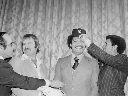 Reggie Jackson grinning on Nov. 29, 1976, as  Yankees' Roy White, right, fits him with a Yankee cap.  The fitting took place at a conference in New York City, held to announce that Jackson had signed a five-year contract with the Yankees. Reportedly, his signature cost the American League champions $ 3 million.  At left is Yogi Berra tapping Jackson as Thurman Munson looks on.
