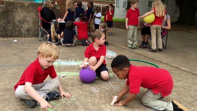 Pre-K students at Cherokee Elementary draw with sidewalk chalk, play ball, hula hoop and have their nails or faces painted Monday during Week of the Young Child.
