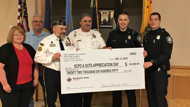 From left, Sandra Justa, Dwynn Delor, Andre Dupuis, Fire Chief David Westrick, Sgt. David Wood and Officer Doug Schneider stand with a ceremonial check benefiting the St. Clair Area Fire Authority and the St. Clair Police Department on Feb. 13, 2018, in St. Clair, Michigan.