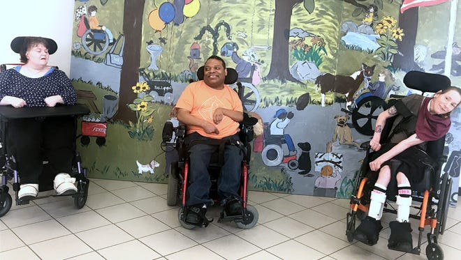 Able2 clients Maryanna Parker, left, Mike Sutherland and Kelly Sullivan pose in front of the mural they helped create, which is now on display at the Arnot Mall.