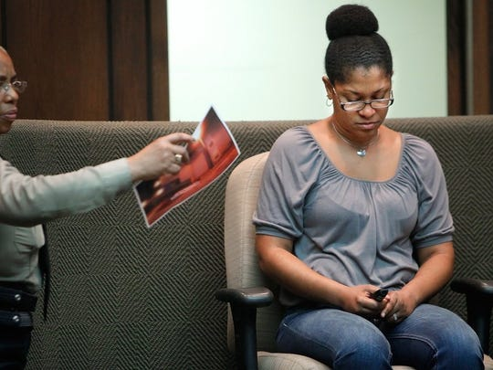 Dionne Lee bows her head after identifying a photo of the body of her fiance, Larry Wilkins, during the murder trial of Martiness Henderson on March 8, 2016.