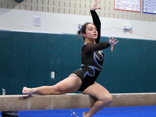 Rebeca Simu performs her routine on balance beam for Plymouth during Tuesday's meet.