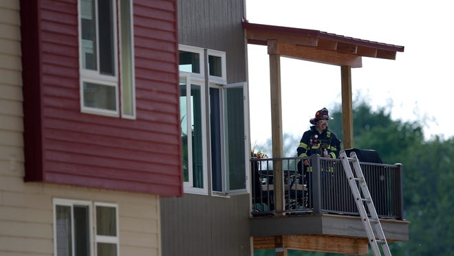 A firefighter stands on the deck of a complex on the 200 block of South Riverheath Tuesday, May 24, 2016 in Appleton.