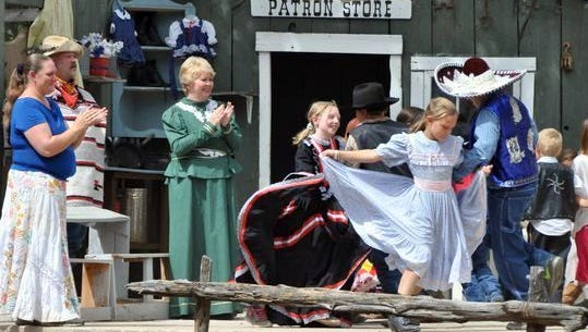 """Children and adults dance on the set of """"The Last Escape of Billy the Kid"""" during the Old Lincoln Days celebration."""