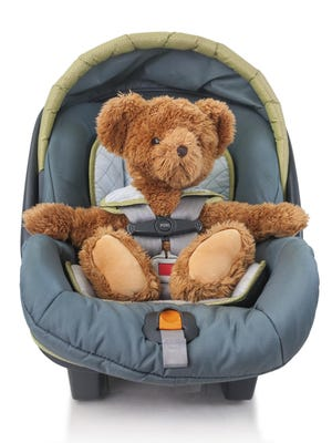 Stock image: Teddybear in a baby car seat.