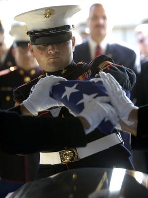 """A Marine helps fold an American flag that was used to cover Cpl. Jonathan """"J.R."""" Spears' casket."""