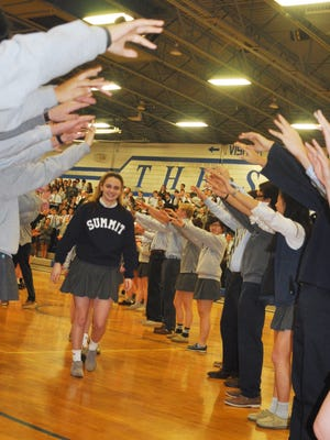 """Junior Ali Miller leads The Summit Country Day School's state diving and swimming contenders through a """"spirit tunnel"""" at the end of a pep rally on Tuesday."""