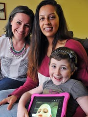Isabella Huffman of Palm Bay, 7, who was diagnosed with Burkitts Leukemia shows a photo of her with no hair. Here she is with her mother Sarah Rogell and Alicia Ortiz, 18, of Melbourne, a student at West Shore Jr Sr High School. Ortiz helped raise more than $5,000 for her senior project called Granting a wish. Isabella and her family will use the money for a dream trip to Disney World.