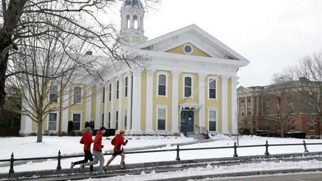 Runners make their way along a sidewalk on the campus of Wheaton College, in Norton, Mass.
