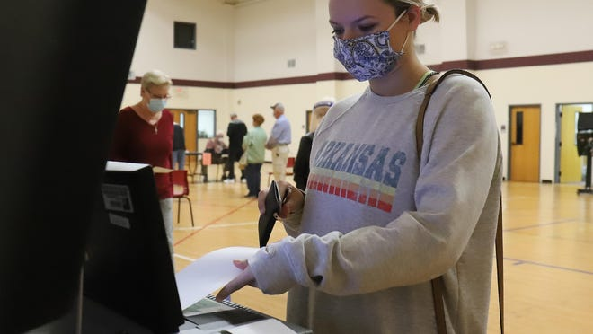 After voting, Mary Autry scans in her ballot at Rye Hill Baptist Church, Monday, Oct. 19, during the first day of early voting in Arkansas.