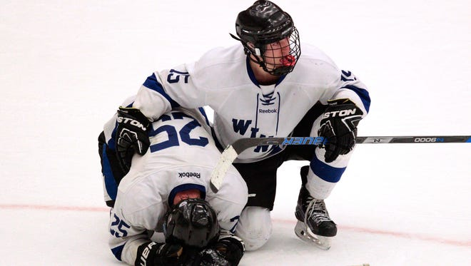 Dejected Waukesha players Wyatt Wilderman (left) and Garrett Wilderman kneel on the ice Saturday after their 2-1 loss to Hudson in the WIAA boys championship game.