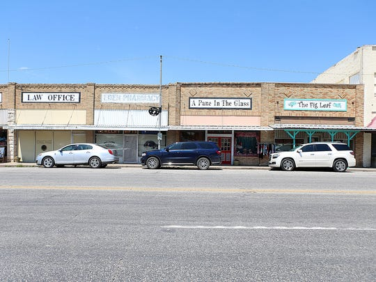 Vacant and operating businesses line the block of the