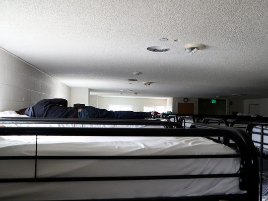 A man sleeps Friday at the Good News Rescue Mission in Redding. Rain and cold weather are expected this weekend, exposing the homeless to harsh outdoor conditions.