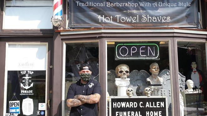 Owner Jessie Van Deinse stands outside his window at the 1886 Barbershop in Somersworth.