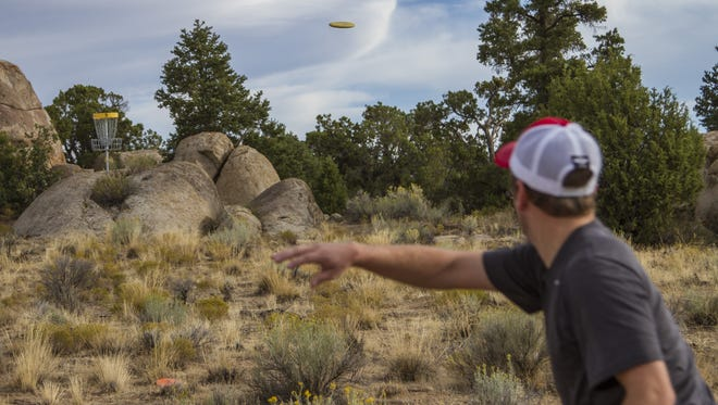 Mason Christison throws a disc near hole  No.5 at Three Peaks Disc Golf Course, Saturday, Sept. 26, 2015.